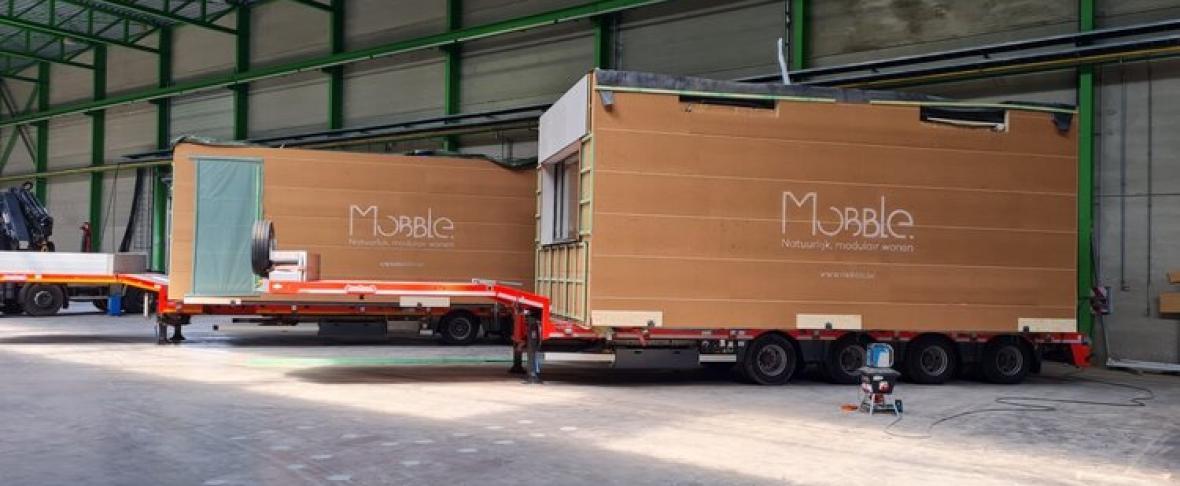 De twee stukken van het inschuifhuis op trailers, klaar voor vertrek.