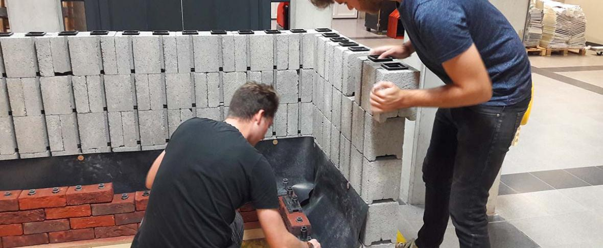 Twee mannen bouwen een muur modulair op